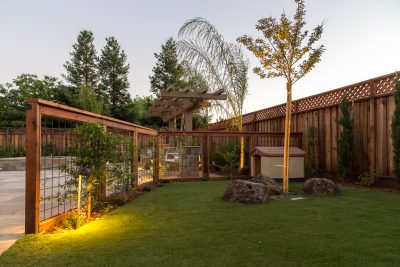 dog house with fence and outdoor lighting