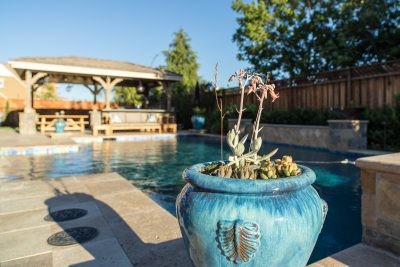 blue stone flower pot near swimming pool