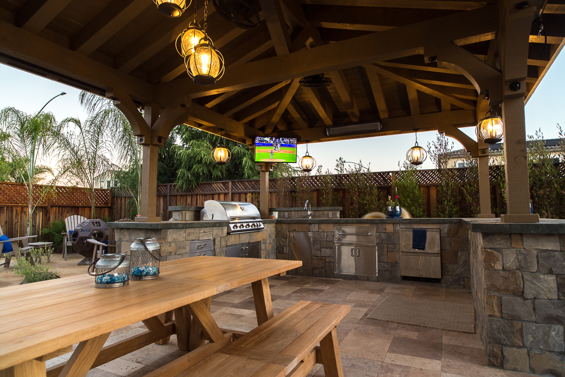custom outdoor kitchen in Morgan Hill with picnic style seating and pergola