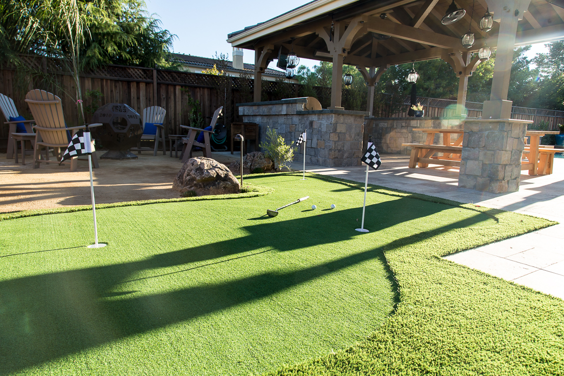 putting green installation in Morgan Hill, California with dramatic shadows and covered outdoor kitchen in background