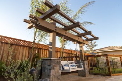 custom hardscape with pergola and swing