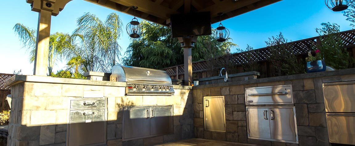 custom outdoor kitchen in Morgan Hill with barbecue, pergola, and flatscreen TV